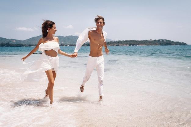 young-beautiful-man-woman-couple-white-clothes-running-along-beach_120960-23