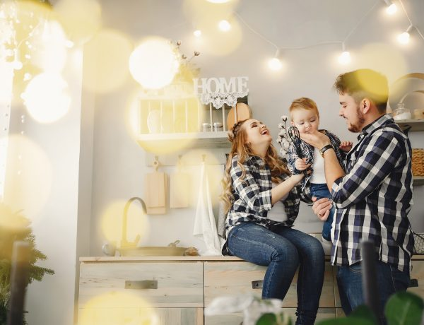 Family on the kitchen. Blonde in a blue shirt. Pregnant woman with her husband and little son