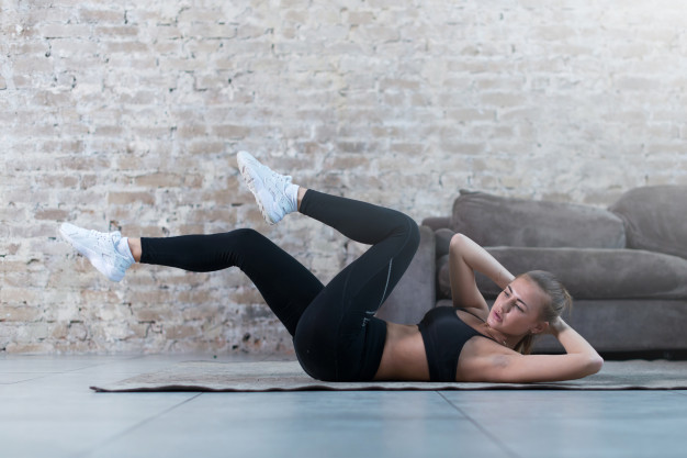 sportive-young-lady-doing-crisscross-crunch-exercise-lying-rug-modern-studio_141192-290